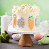 Carrot cake with frosting for Easter. Carrot cake with cream cheese frosting for Easter decorated with cookies Royalty Free Stock Photo