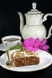 Carrot cake with a cup of tea. Slice of carrot cake with a cup of tea, teapot and pink azaleas. Served on light-colored china with gold trim on a black Royalty Free Stock Photography