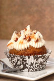 Carrot cake cupcake with cream cheese frosting. Delicious carrot cake cupcake with cream chees frosting, toasted coconut and chopped pecan nuts royalty free stock images