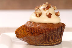 Carrot cake cupcake with cream cheese frosting. Delicious carrot cake cupcake with cream chees frosting, toasted coconut and chopped pecan nuts stock image