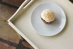 Carrot Cake Cupcake. With cream cheese frosting and coconut shavings on top royalty free stock photography