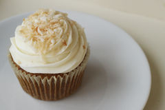 Carrot Cake Cupcake. With cream cheese frosting and coconut shavings on top royalty free stock image