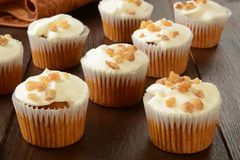 Carrot cake cupcakes. Small carrot cake cupcakes on a rustic wooden table Royalty Free Stock Photography