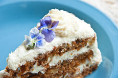 Carrot cake with edible violet blossoms Stock Photos