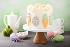 Carrot cake with frosting for Easter. Carrot cake with cream cheese frosting for Easter decorated with cookies Stock Photography