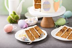 Carrot cake with frosting for Easter. Carrot cake with cream cheese frosting for Easter decorated with cookies Stock Images
