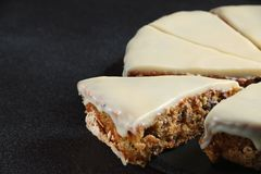 Carrot cake with icing on dark background close up stock photos