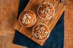 Carrot cake muffins with nuts, raisins and oats on a wooden back. Ground Royalty Free Stock Images