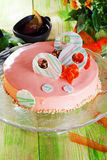 Carrot cake in pink icing decorated with white chocolate still life plank wooden table decorations Dried carrots romantic spring f Stock Photography