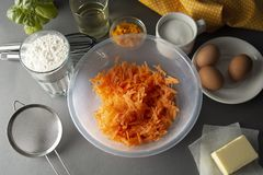 Carrot cake recipe. Making dough for carrot cake, pie, muffins or tart, on kitchen table - eggs, flour, butter, orange, citrus,. Oil sugar Flat lay royalty free stock photography