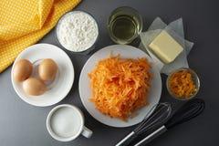 Carrot cake recipe. Making dough for carrot cake, pie, muffins or tart, on kitchen table - eggs, flour, butter, orange, citrus,. Oil sugar Flat lay stock photo