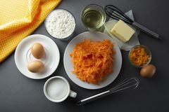 Carrot cake recipe. Making dough for carrot cake, pie, muffins or tart, on kitchen table - eggs, flour, butter, orange, citrus,. Oil sugar Flat lay royalty free stock images