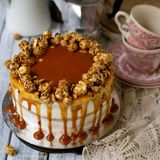 Carrot cake with salted caramel and cheesecake inside, decorated with popcorn and caramel. Retro style, vintage. Selected focus, royalty free stock image