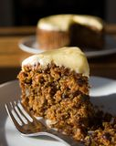 Carrot cake slice with cake in background. A delicious slice of freshly baked carrot cake on a plate with a fork. Short depth of field, with whole cake visible Royalty Free Stock Photos