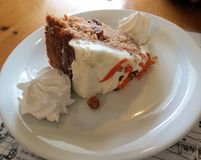 Carrot Cake. A slice of carrot cake, with creamy frosting, garnished with dollops of whipped cream royalty free stock image