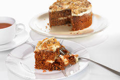 Carrot cake slice served on a plate with fork on a white surface Royalty Free Stock Photography