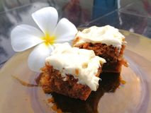 Carrot cake. Two slices of carrot cake on a plate with frangipani flower on the side Stock Photos