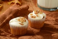 Carrot cakr cupcakes. Small carrot cake cupcakes with frosting and a glass of milk Stock Photos