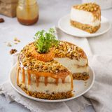 Carrot cheesecake with walnuts and caramel and cut piece of cake. On a plate stock images