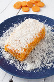 Carrot and coconut cake close up. Piece of carrot and coconut cake with some layers of cookies, covered with grated coconut in a blue plate on a white weathered Stock Photography