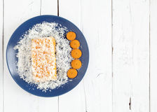 Carrot and coconut cake on white table. Piece of carrot and coconut cake cover with grated coconut in a blue plate with some carrot slices on a white weathered Stock Photo