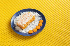 Carrot and coconut cake with yellow background. Piece of carrot and coconut cake with some layers of cookies, covered with grated coconut in a blue plate with Stock Photo