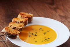 Carrot creamy soup. Creamy carrot - ginger soup with cereal rolls croutons Stock Photo