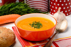 Carrot creme soup in orange bowl on the table. Stock Photography