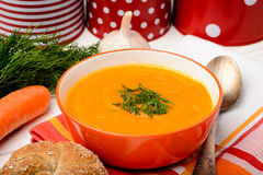 Carrot creme soup in orange bowl on the table. Royalty Free Stock Photo