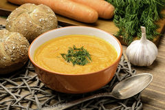 Carrot creme soup in orange bowl on the table. Stock Image