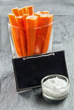 Carrot crudites with savory dip and a slate. Carrot crudites cut into thin batons in a glass container served with a savory dip and a blank school slate for your Royalty Free Stock Photography