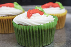 Carrot cupcakes in green and yellow casings. Sweet carrot cupcakes  make with white cream cheese frosting and trimmed with orange and yellow carrot design Stock Photo