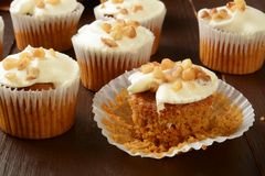 Carrot cupcakes with nuts. Several carrot cupcakes with nuts and frosting on a rustic wooden table Royalty Free Stock Images