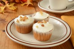 Carrot cupcakes. Topped with nuts and served with a cup of coffee Royalty Free Stock Photography