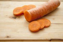 Carrot cut. Onto edge board Stock Photos