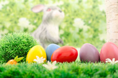 Carrot and Easter eggs. Colored easter eggs by a tree in the forest. Blurred Easter bunny Royalty Free Stock Photo