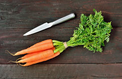 Carrot. Fresh carrot packet and iron knife on wood table background. Tasty and health product. Root vegetable Royalty Free Stock Photography
