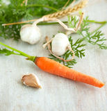 Carrot, garlic and ear of wheat Stock Photo