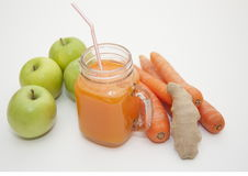 Carrot, ginger and apple smoothie. Mason glass jar with orange smoothie and whole fresh green apples, carrots and ginger root Stock Photography