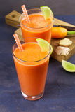Carrot ginger smoothie, garnished with lime. Carrot ginger smoothie, garnished with lime Stock Images