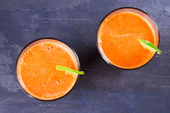 Carrot ginger smoothie, garnished with lime. View from above, top studio shot Stock Photography