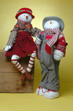 Carrot girl and boy. A cute holiday theme couple with a sock full of gifts pose II with her arm around his shoulder Royalty Free Stock Image