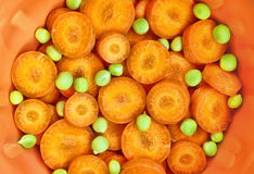 Carrot and green peas in ceramic ware Royalty Free Stock Images
