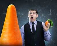 Carrot in hand and hude at a distance Royalty Free Stock Photo