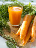 Carrot juice. Glass of fresh carrot juice and some fresh vegetables Royalty Free Stock Photography