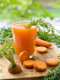 Carrot juice. Glass of fresh carrot juice and some fresh vegetables Royalty Free Stock Images