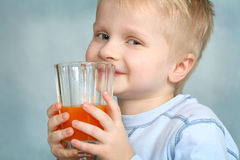 Carrot Juice. A young boy drinking carrot juice Royalty Free Stock Images
