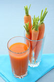 Carrot juice. Glass of fresh carrot juice and some fresh vegetables Royalty Free Stock Photos