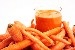 Carrot Juice. A glass of carrot juice and carrots against white background Royalty Free Stock Images