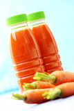 Carrot juice. Two bottles of carrot juice and some fresh carrots Royalty Free Stock Photography